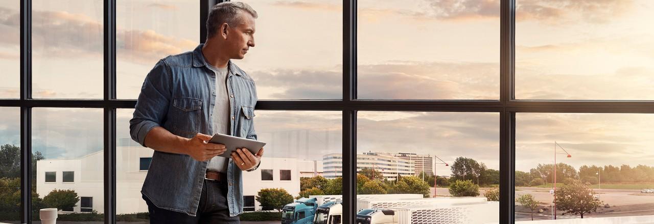 Un bărbat care ține în mână o tabletă stă lângă o fereastră și privește în jos spre flota de autocamioane