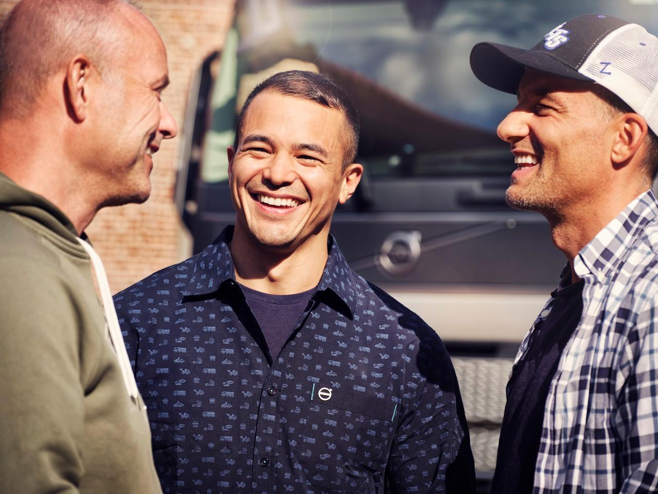 Trei bărbați care zâmbesc în fața unui autocamion Volvo