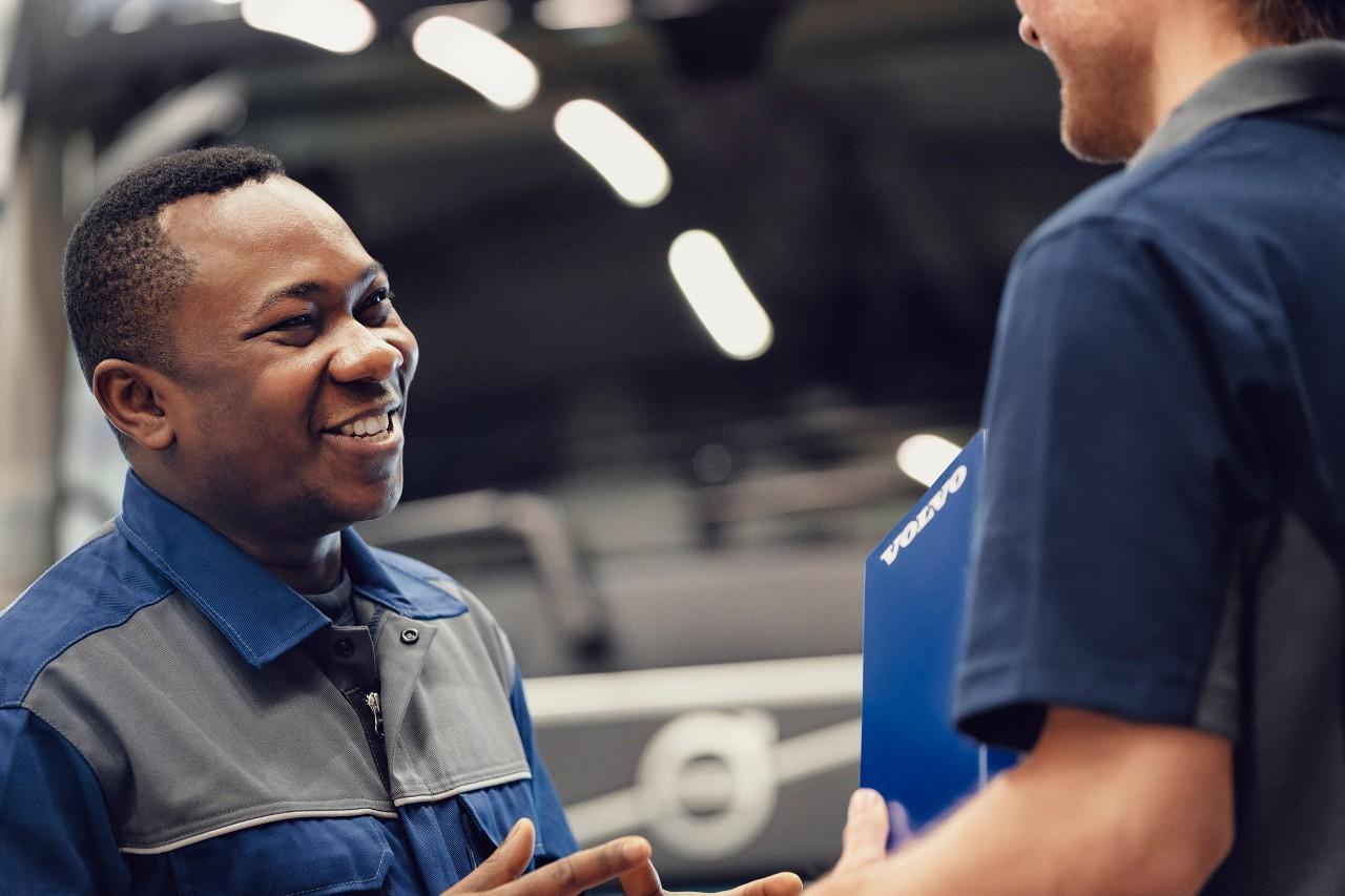 Un tehnician de service Volvo discută vesel cu un coleg